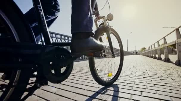 Low angle tracking shot of a businessman riding a bicycle over a bridge towards a bright sun.