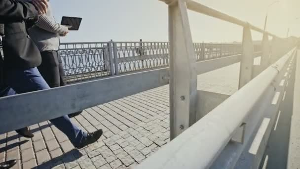 Two man walking on a pedestrian walkway across a bridge viewed from the adjacent road tilting up from the guard rail to a full length view in a tracking shot.