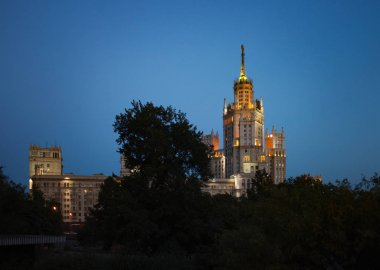 The High-rise building on the Kotelnicheskaya Embankment of Moskva river called Stalin skyscraper with the citylights on the blue sky at evening or night.