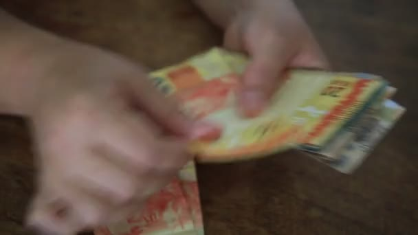 salvador, bahia / brazil - march 28, 2020: womans hands hold reais banknotes, currency used in Brazil.