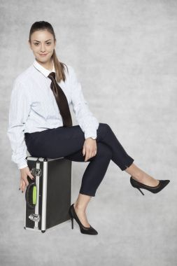businesswoman resting sitting on a suitcase, smiling face