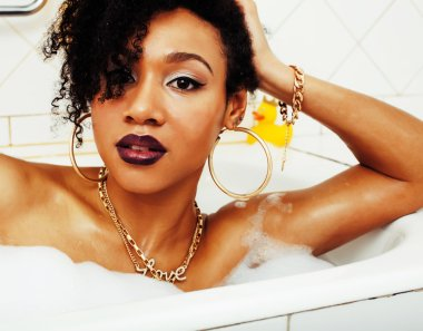 young afro-american girl laying in bath with foam