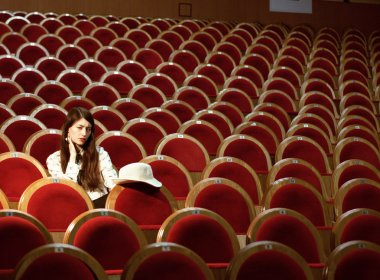 portrait of a pretty girl hipster in a movie theater wearing hat, dreaming alone