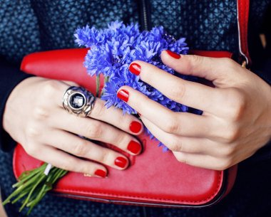 manicured hands holding handbag and cornflowers