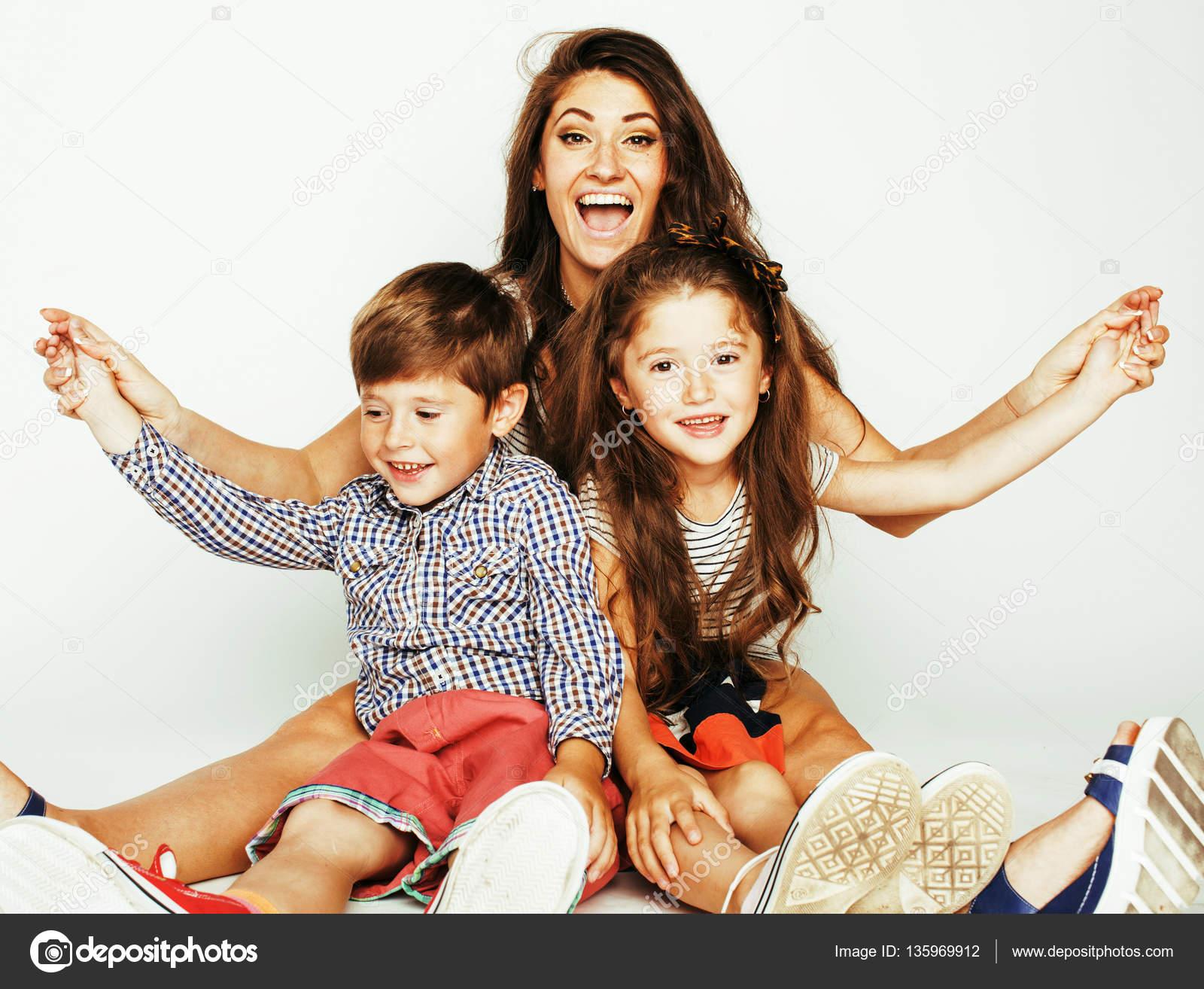 junge mutter mit zwei kindern auf wei em hintergrund gl cklich l chelnd familie indoor. Black Bedroom Furniture Sets. Home Design Ideas