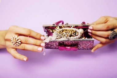 woman hands holding handbag with jewelry