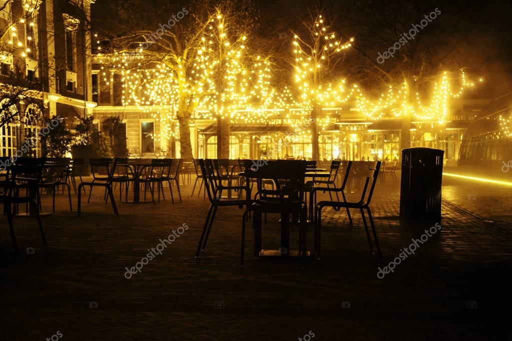 empty night restaurant, lot of tables and chairs with noone, magic fairy lights on trees like christmas celebration