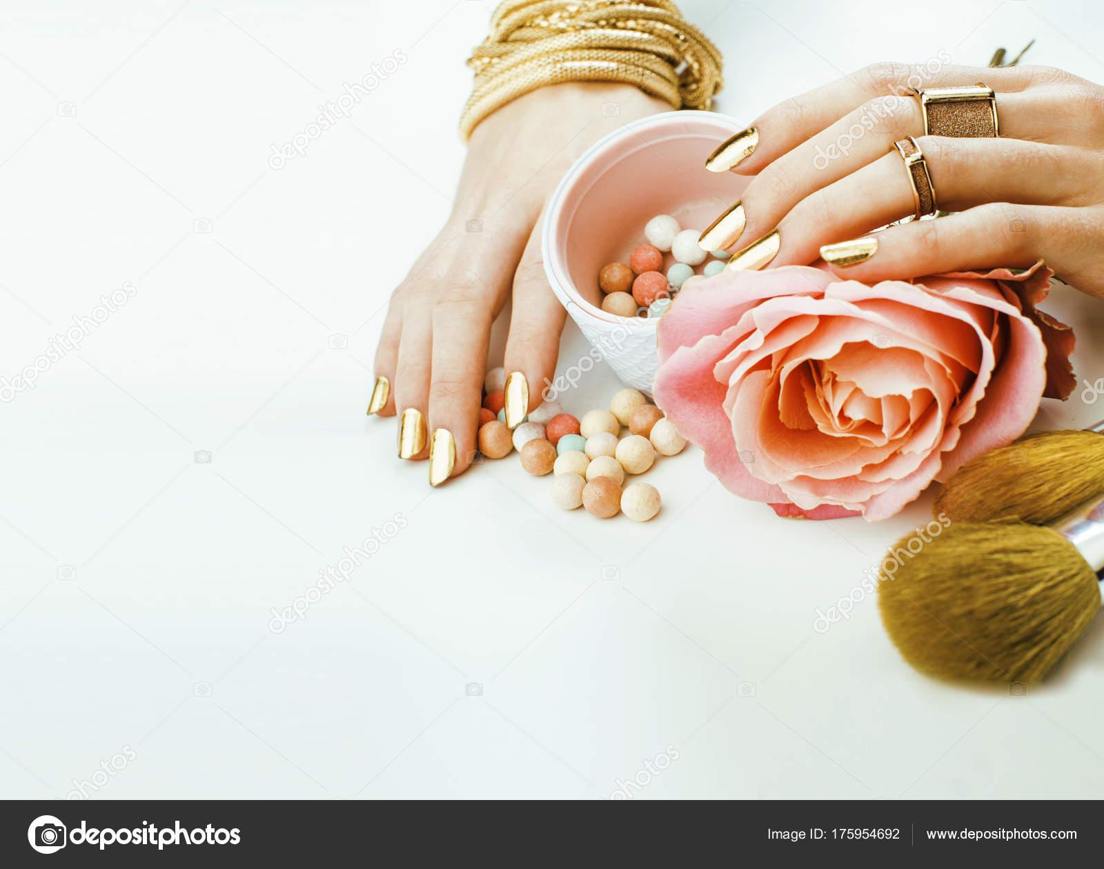 0d61ebf898b6 Žena ruce zlatý manikúru a mnoho kruhy těsně drží štětce