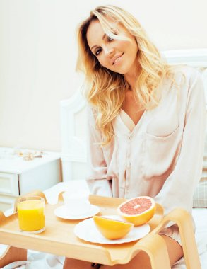 young beauty blond woman having breakfast in bed early sunny mor