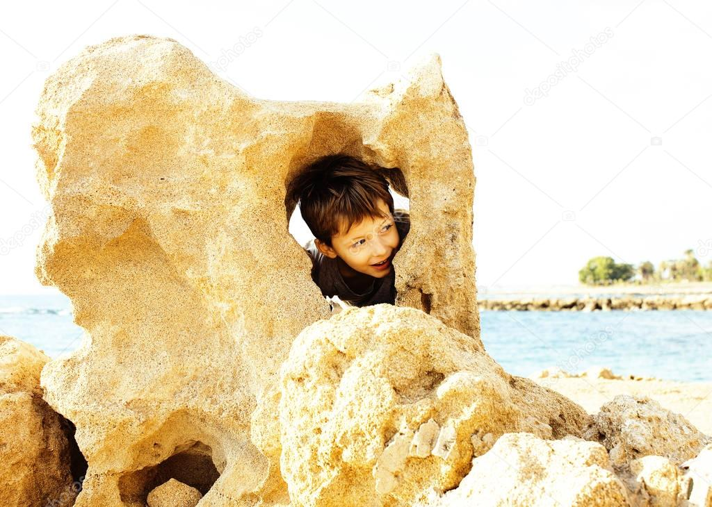 little cute boy on sea coast thumbs up playing with rocks