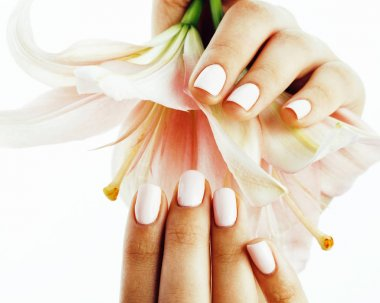 beauty delicate hands with manicure holding flower lily close up