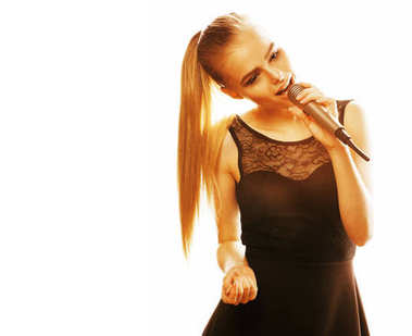 young pretty blond woman singing in microphone isolated close up