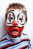 Fotografie malý roztomilý chlapec s facepaint jako klaun, pantomimickou výraz