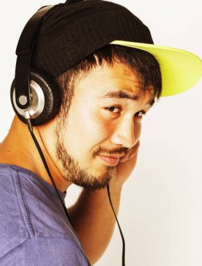 young asian man in hat and headphones listening music on white b