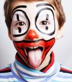 Fotografie malý roztomilý skutečného chlapce s facepaint jako klaun, pantomimickou expre