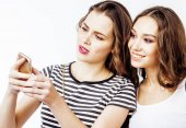Fotografie two best friends teenage girls together having fun, posing emotional on white background, besties happy smiling, making selfie, lifestyle people concept