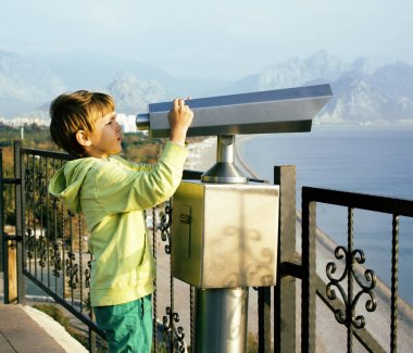 little cute boy looking through telescope at sea viewpoint in At