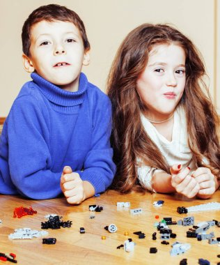 funny cute children playing toys at home, boys and girl smiling,