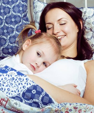 Portrait of mother and daughter laying in bed and smiling close