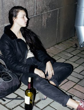 young poor ttenage girl sitting at dirty wall on floor with bott