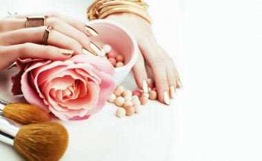 woman hands with golden manicure and many rings holding brushes, makeup artist stuff stylish, pure pink flower rose among cosmetic for makeup