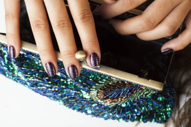 woman hands with shiny manicure holding little purse peacok feather, cosmetic and fashion people concept