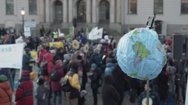 A blow-up globe being held at a climate protest full of people.