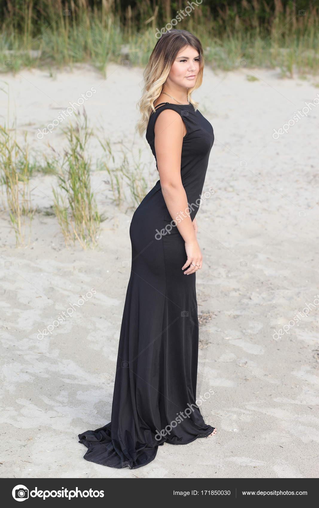 6ee06f1e92ee donna in vestito nero lungo sulla spiaggia di sabbia — Foto Stock ...