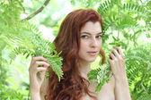 Fotografie portrét mladé krásné ženy se zelenými listy