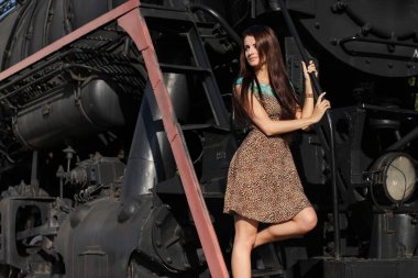 young fashionable girl in a dress on an old steam train