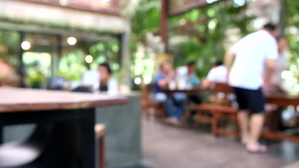 Blur image or defocus of customer outside coffee shop and restaurant for green natural screen