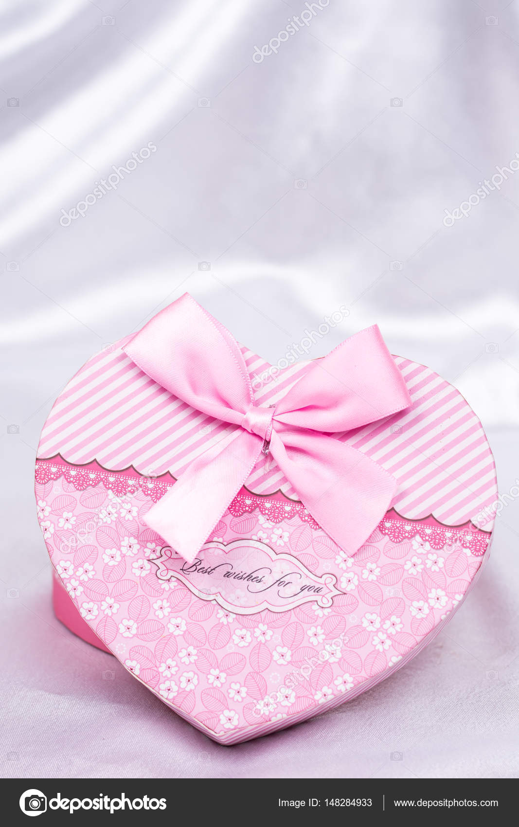 Heart shaped gift box with bow over white satin — Stock Photo ...