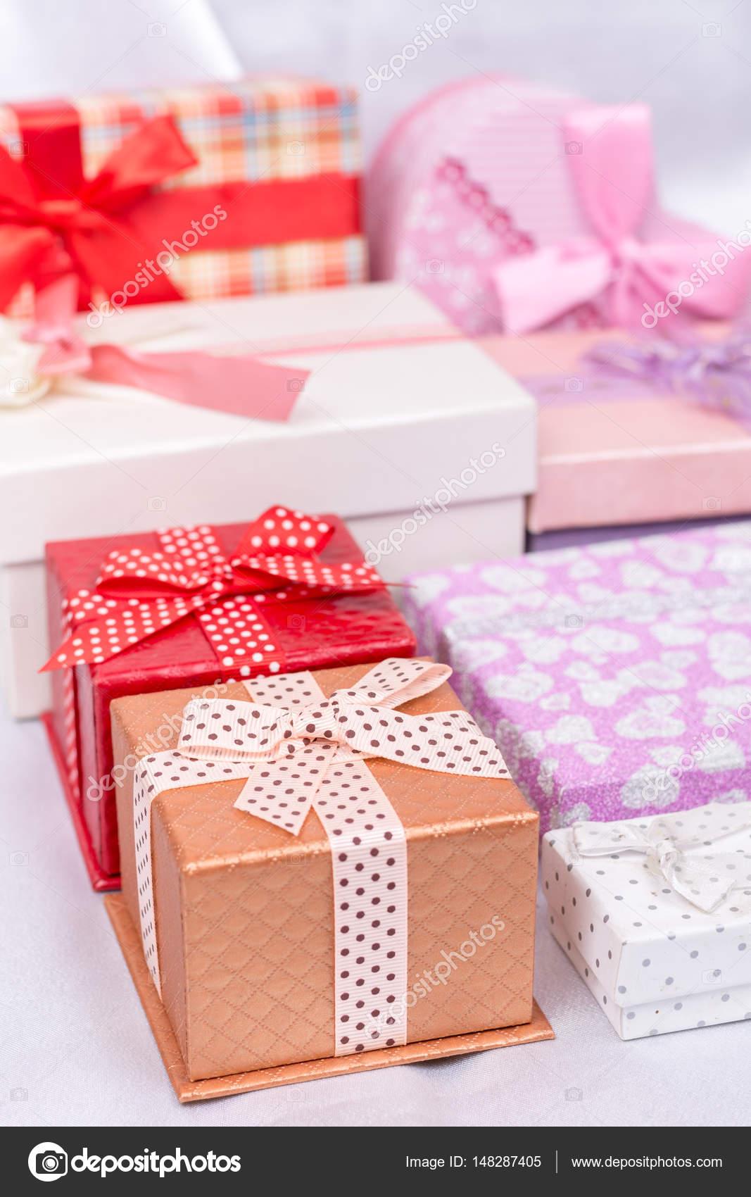 Pile of gift boxes with bows over white satin — Stock Photo © zlaja ...