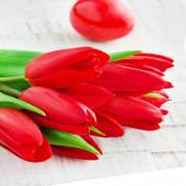 Fotografie rote Tulpen mit roten Ostereiern auf einem hölzernen Hintergrund