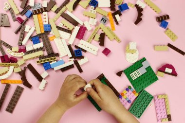 Child playing with colored blocks on a pink background, hands close-up