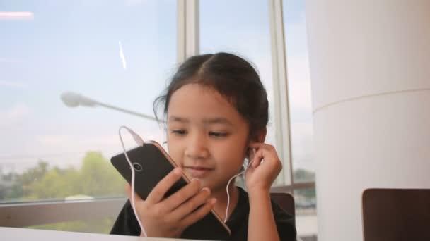 Asijská holčička pomocí smartphone s sluchátka a sedí u okna skla