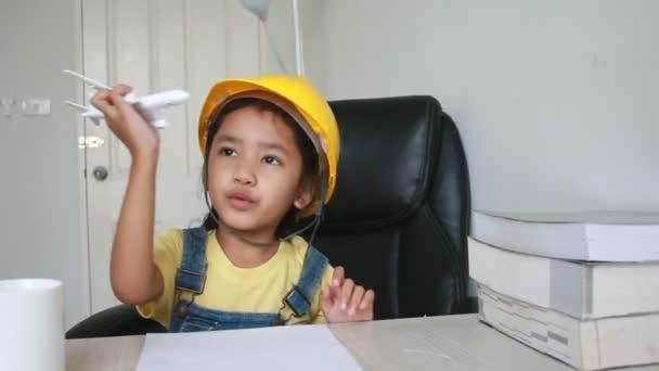 asiatisches kleines Mädchen mit gelber Ingenieursmütze spielt Flieger