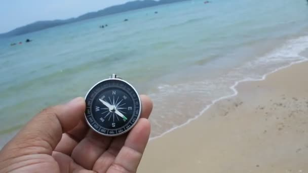 Close up shot hand of mand holding a compass on the  sand beach with nature sea and wind ambient sound