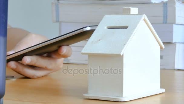Händen Frau Smartphone-Computer verwenden und, Geld Münze ins Sparschwein Haus Metapher Mobilanwendung Berechnung für Geld zu sparen für kaufen Haus und Immobilien Konzept wählen Sie Schwerpunkt Haus