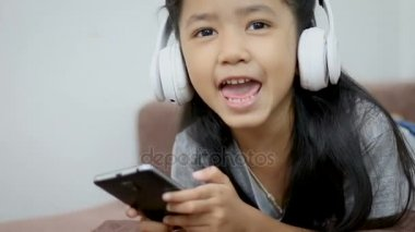 Asian little girl listen to the music by white wireless headphone with happiness talk thumb up and look at camera