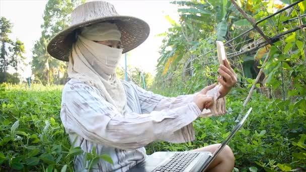 4K Farmer using smartphone and laptop computer to video conference and chat, social media technology concept
