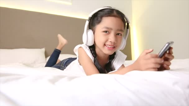 Asian little girl listening white head phone and mobile smartphone with happiness on the bed