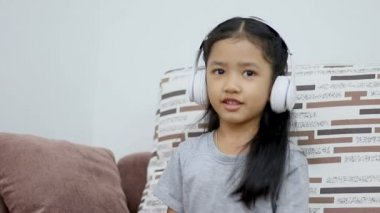 Asian little girl using white wireless headphone with happiness