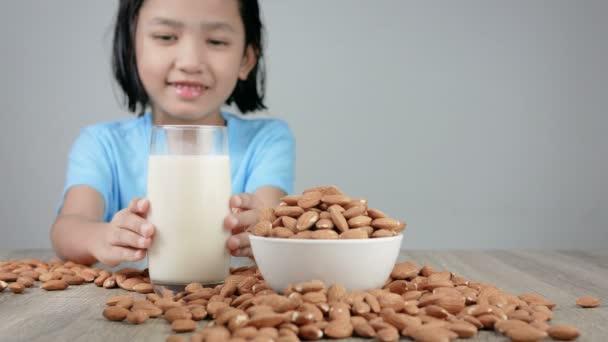 Asijská holčička pít mandlové mléko vybrat zaměření na mléčné sklo