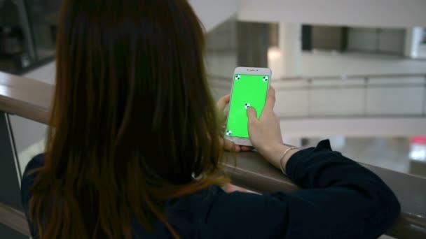 ruce drží a pomocí klíče chrom smartphone podnikání. prsty si gesta na zelené klíčové displej pro chytrý telefon základních funkcí