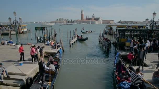 Venice, Olaszország - 2017 május: Két gondolák kikötve a velencei San Giorgio Maggiore templommal a háttérben, ködös nap, Velence, Olaszország. Kézi lövés