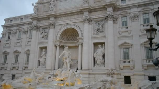 The famous Trevi Fountain Fontana di Trevi in Rome, designed by Nicola Salvi in Baroque and Rococo fashion. Wide shot of the fountain and detail of a sculpture of horses.