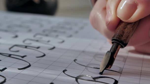 Kalligraphie auf Sonnenlicht. Schreiben mit Federhalter, schwarze Tinte auf weißem Papier. Großbuchstabe B. Filmische Nahaufnahme.