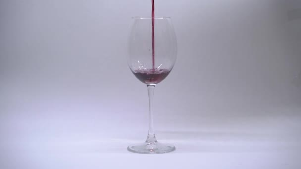 Red wine pouring in wine glass over white background. Slow motion