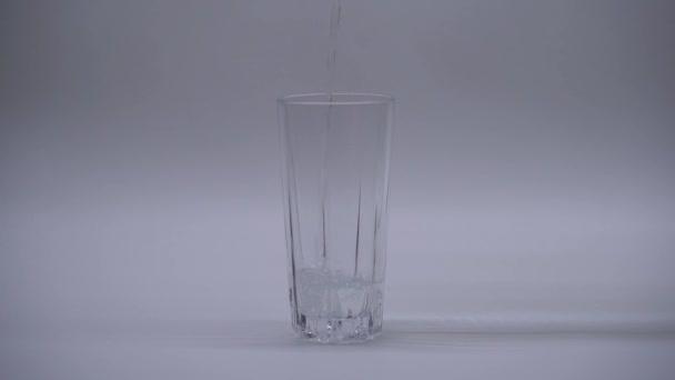 Nalévání vody do sklenice, izolace na bílém pozadí, zpomalené záběry